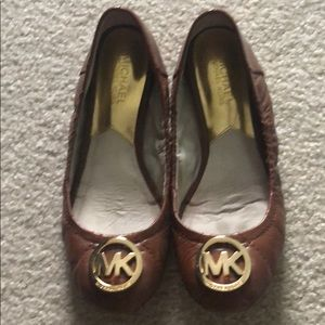 Michael Kors brown flats with gold symbol. Size 6